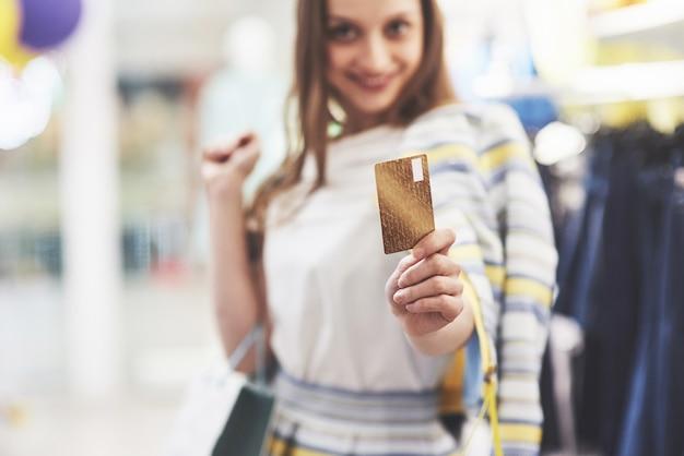 店で買い物袋とクレジットカードを持つ幸せな女性。すべての女性のお気に入りの職業、ライフスタイルのコンセプト。