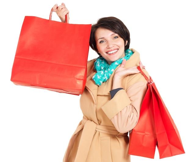 Donna felice con le borse della spesa in cappotto beige autunno con sciarpa verde isolato su bianco