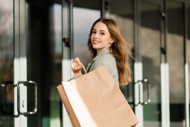 ショッピングを楽しんで買い物袋を持つ幸せな女性。消費主義、ライフスタイルの概念