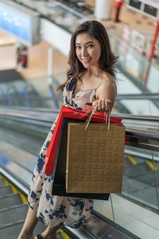 Happy woman with shopping bags on escalator in mall