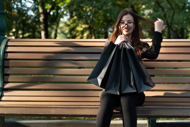 Счастливая женщина с хозяйственными сумками на скамейке в парке после успешных покупок.