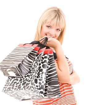 Счастливая женщина с хозяйственными сумками над белой