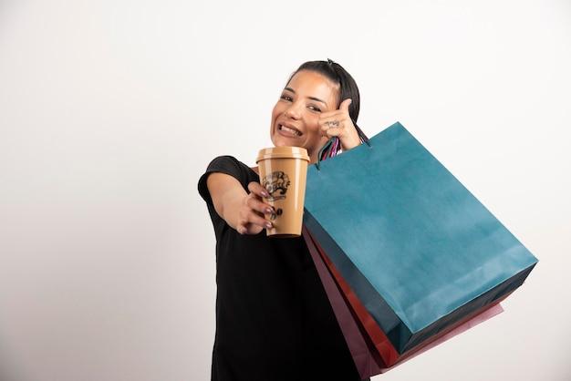 Donna felice con i sacchetti della spesa che mostra tazza di caffè alla macchina fotografica.