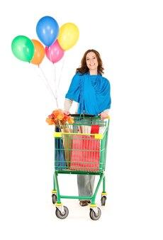 Счастливая женщина с тележкой для покупок и воздушными шарами над белой стеной