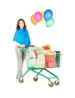 쇼핑 카트 및 흰색 위에 풍선 행복 한 여자