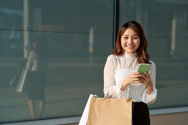 쇼핑 행복한 여자, 스마트 폰을 사용하여 쇼핑을 즐기는 야외 서있는 동안 쇼핑 가방을 들고 웃는 여자