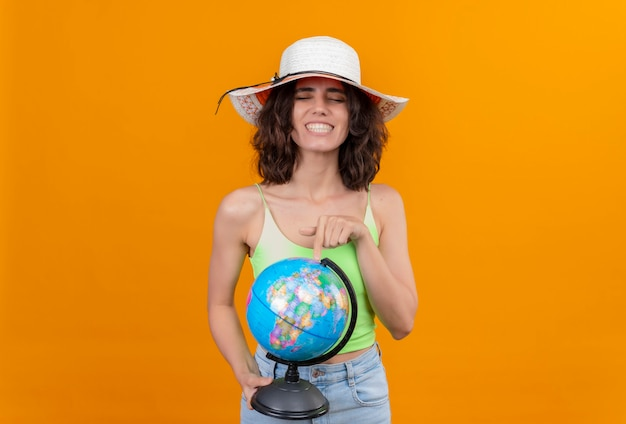 Una donna felice con i capelli corti in cima verde del raccolto che porta il cappello del sole che indica un globo con il dito indice
