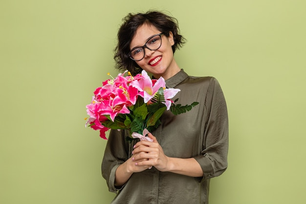 Счастливая женщина с короткими волосами, держащая букет цветов, глядя в камеру, весело улыбаясь, празднует международный женский день 8 марта, стоя на зеленом фоне