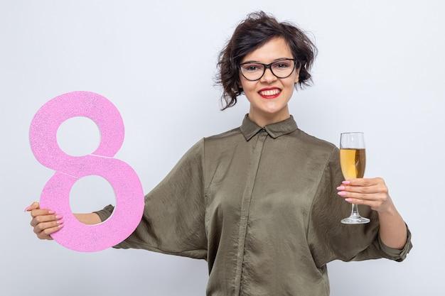 골판지와 샴페인 잔으로 만든 8 번을 들고 짧은 머리를 가진 행복한 여자는 국제 여성의 날 3 월 8 일을 즐겁게 웃고 카메라를보고 웃고 있습니다.