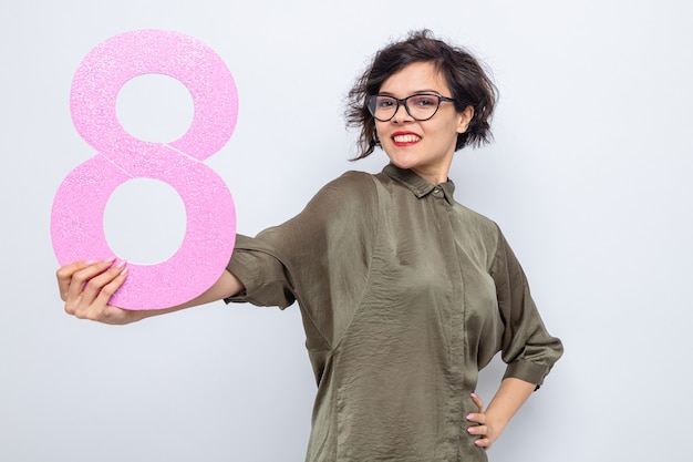 Happy woman with short hair holding number eight made from cardboard looking at camera smiling confident celebrating international women's day march 8 standing over white background