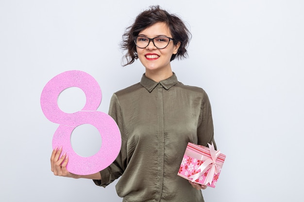 Happy woman with short hair holding number eight made from cardboard and present looking smiling cheerfully celebrating international women's day march 8
