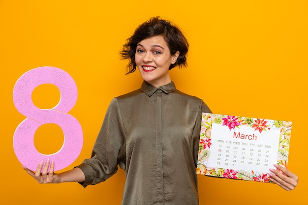 Happy woman with short hair holding paper calendar of month march and number eight looking smiling cheerfully celebrating international women's day march 8