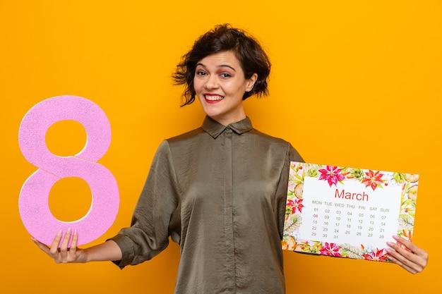 Счастливая женщина с короткими волосами держит бумажный календарь месяца март и номер восемь, весело улыбаясь, празднует международный женский день 8 марта