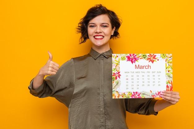 オレンジ色の背景の上に立って国際女性の日3月8日を祝って元気に親指を見せて笑顔のカメラを見て月の行進の紙のカレンダーを保持している短い髪の幸せな女性