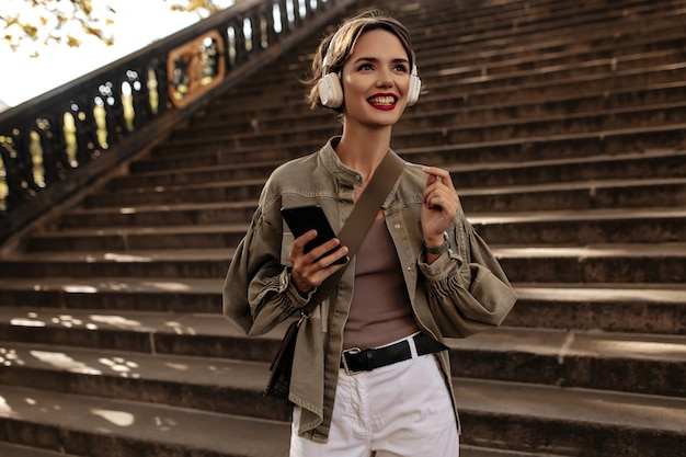 Happy woman with short hair and red lips in headphones smiles. woman in jacket and light pants holds phone outdoors.