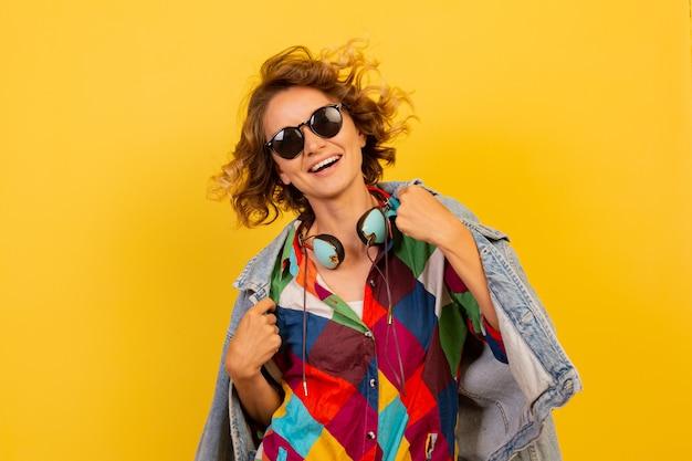 イヤホンで音楽を聴き、黄色の壁を楽しんでいる短い髪型の幸せな女性