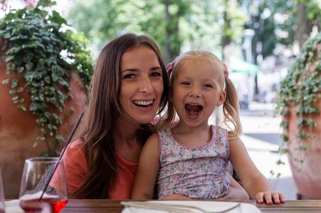 식당 테이블 뒤에 작은 금발 소녀 소리와 함께 행복 한 여자.