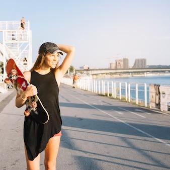Happy woman with skateboard walking on street
