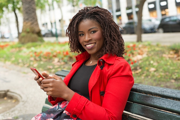Happy woman with smartphone smiling