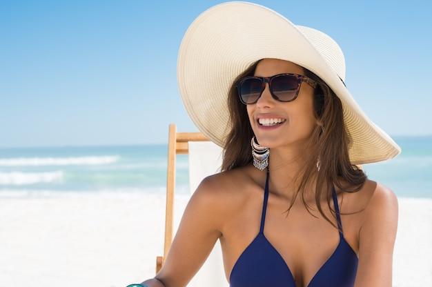 ビーチで麦わら帽子と幸せな女 Premium写真