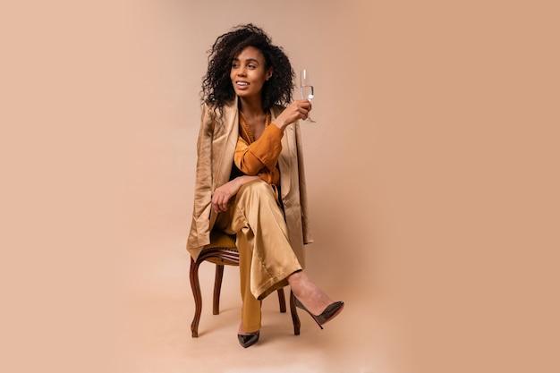 ワインのグラスを保持し、ヴィンテージの椅子ベージュの壁に座っているエレガントなオレンジ色のブラウスとシルクのズボンを身に着けている完璧な巻き毛の日焼けした肌を持つ幸せな女性。