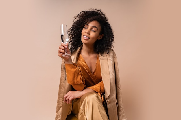 Happy  woman with tan skin with perfect curly hairs  holding glass of wine ,wearing ielegant orange blouse and silk pants sitting on vintage chair  beige wall.