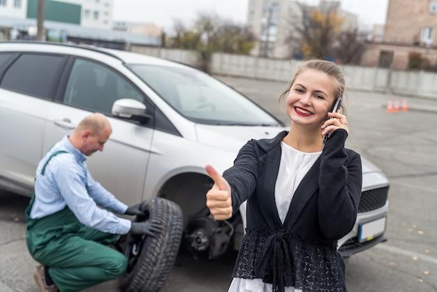 車のサービスに親指を立てて幸せな女性