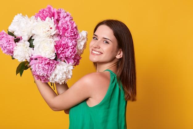 Счастливая женщина с зубастой улыбкой, держа в руках цветы пионов, позирует