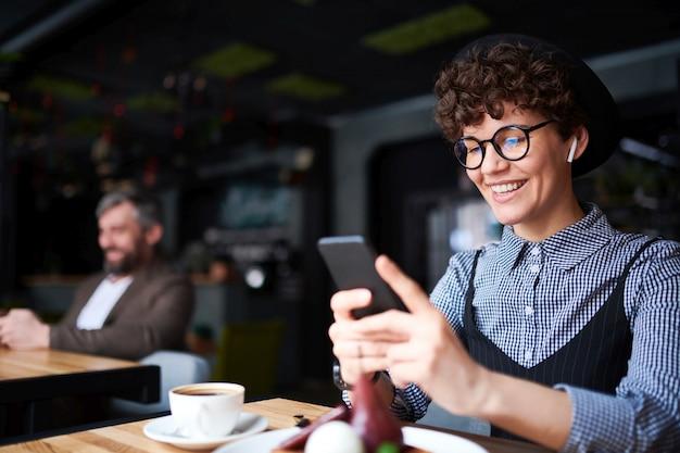 Счастливая женщина с зубастой улыбкой прокручивает в своем смартфоне, проводя время в уютном кафе