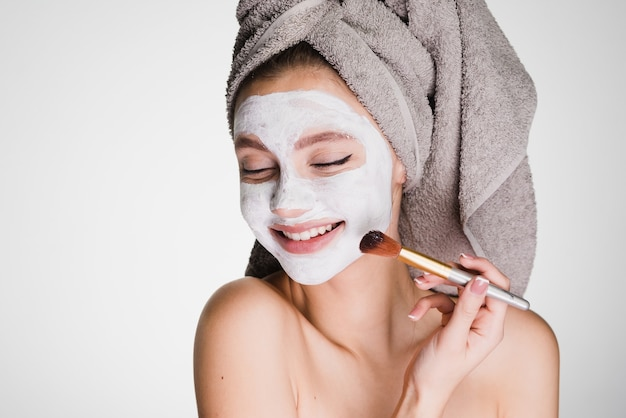 Happy woman with towel on her head after shower apply on face mask skin
