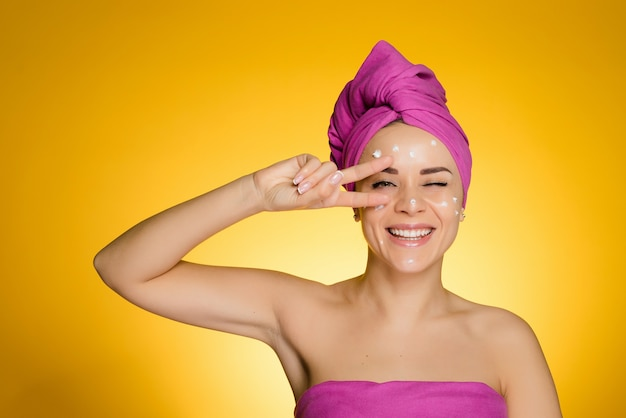 Happy woman with a towel on her head applied cream on her face