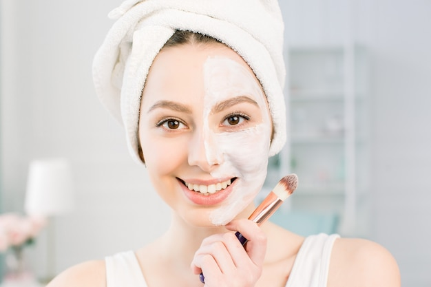 Happy woman with a towel on her head apply a cleansing mask on her face
