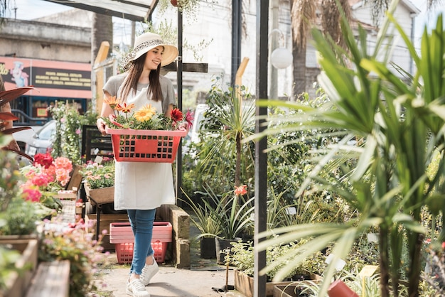 Happy woman with tray of beautiful flowers standing in greenhouse