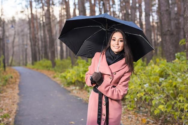 秋の自然の中を散歩中に雨の下で傘を持った幸せな女性