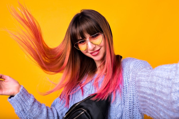 Happy woman with unusual pink hairs making selfie at yellow wall, stylish cozy sweater and hearted vintage sunglasses.