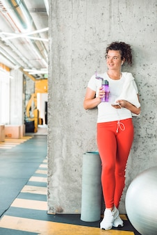 Happy woman with water bottle and smartphone leaning on wall in fitness club