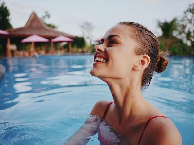 濡れた髪の幸せな女性は自然の中でプールで泳ぐ