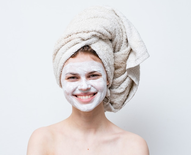 彼女の顔に白いマスクを持つ幸せな女性裸の肩は頭にきれいな肌タオル