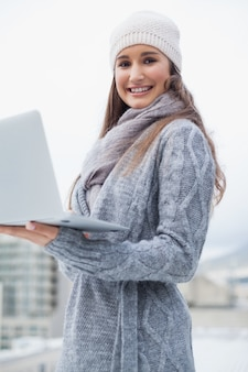 Happy woman with winter clothes on using her laptop
