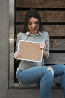 Happy woman with wood tablet