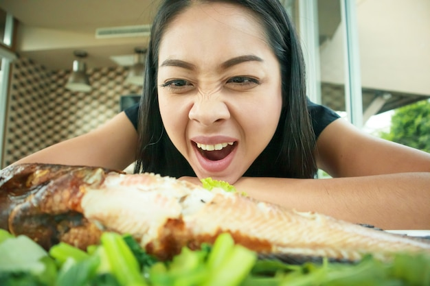 Happy woman with wow face look at grilled fish.