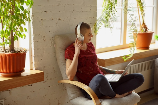Счастливая женщина, работающая из дома во время карантина коронавируса или covid-19, концепция удаленного офиса. красивая лысая модель, менеджер выполняет задачи с ноутбуком, телефоном, проводит онлайн-конференцию, встречу.