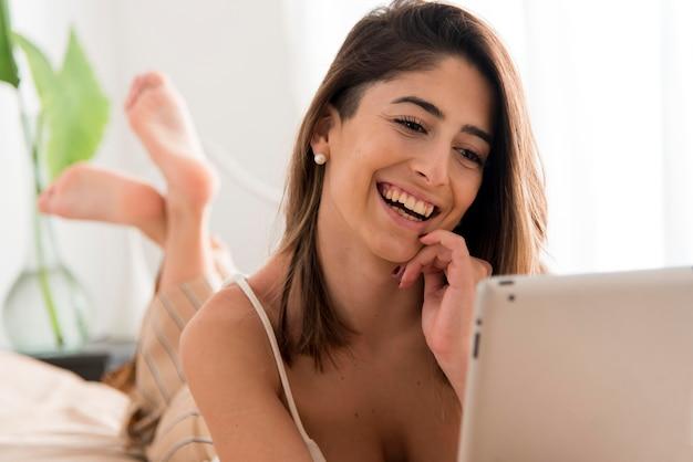 Счастливая женщина работает на планшете