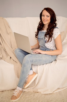 Happy woman working online remotely from home on a laptop
