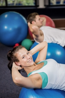 Happy woman working out on fitness ball