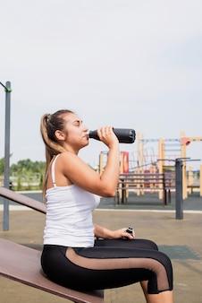 화창한 여름날 운동장에서 운동하는 행복한 여성, 병에서 물을 마시는