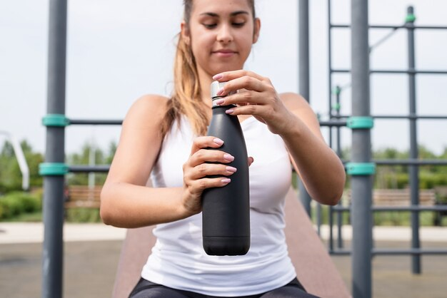 Happy woman working out on the sports ground in sunny summer day, drinking water from the bottle