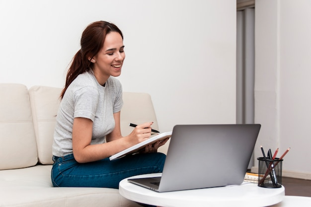 Happy woman working while looking at laptop
