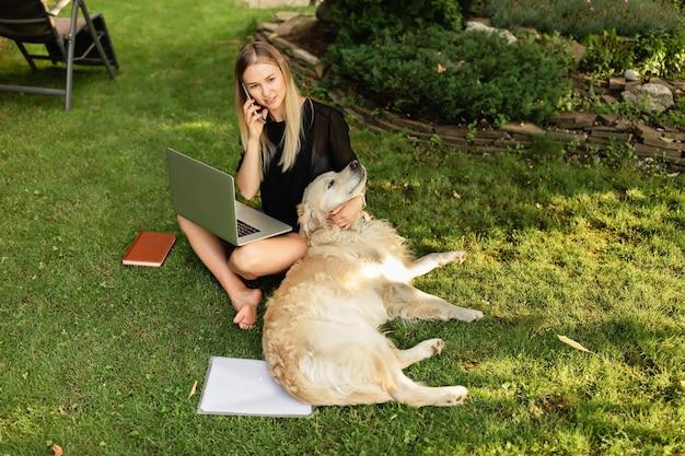 Счастливая женщина работает с ноутбуком и играет с собакой лабрадор на открытом воздухе