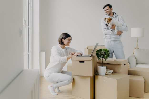 Happy woman works remotely on laptop computer, has happy smile, glad husband in casual clothes plays with pet, spend free time at their new home, surrounded with cardboard boxes in middle